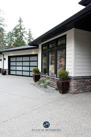 hardiboard cobblestone with black trim and stone exterior garage doors and black soffits kylie