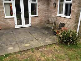 replacing a tired old patio with a new patio in light coloured slabs this patio also features drainage and small steps up onto the lawn area