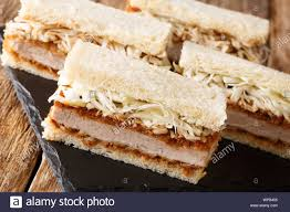 Katsu Sando sandwiches with pork cutlet, tonkatsu sauce and cabbage closeup  on a slate board on a wooden table. horizontal Stock Photo - Alamy