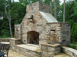 traditional lighting above outdoor stone fireplace and small water curtains facing black furnitures color