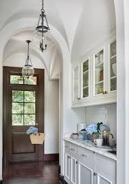 stunning butler s pantry features a barrel ceiling dotted with small amphora bell jar pendants illuminating glass front upper cabinets and white bottom