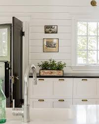black and white cottage kitchen features a white shaker cabinets adorned with brass vintage pulls paired with honed black countertops and a horizontal