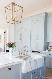 kitchen powder blue cabinets black gold vent hood marble countertops calcutta gold marble open shelves black barstools brass fixtures lantern 7 of 7