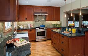 oak mission cabinets with black cup pulls and hardwood floors and dark granite countertops