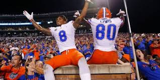 florida wide receiver trevon grimes 8 and tight end c yontai lewis 80 lead their fans as the team celebrates a 13 6 win over mississippi state in an