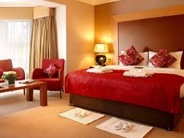 trendy red covers master bed sheet also red fabric accent chairs and tables as well as neutral brown wall painted as modern best colors for bedrooms