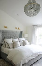 white and gray bedroom with beaded chandelier