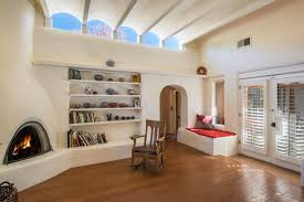 sitting area of owners bedroom with kiva fireplace and coved ceiling