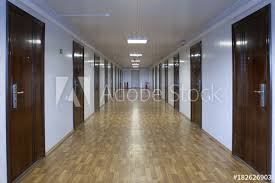 office hallway. Long Office Hallway With Many Doors Of Dark Red Wood.