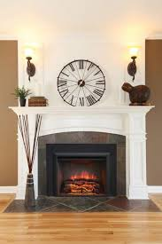 artistic white faux stone electric fireplace including large roman numeral wall clock between wall mount light