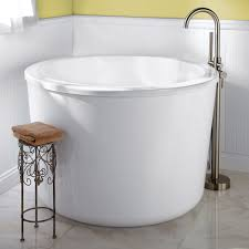 round japanese soaking tubs for small bathrooms with curved steel faucet and wrought iron shower caddy