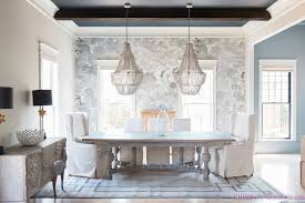 dining room double beaded chandelier skirted parsons chair wingback chair surya rug nuvolette cloud wallpaper fornasetti black ceiling faux beams