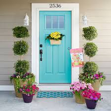 entry with door mounted basket of daisies