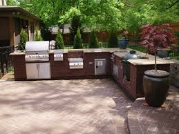 l shape brick outdoor kitchen with smoker on paving stone floor