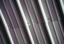 closeup photo of overlapping corrugated steel sheets fastened with s