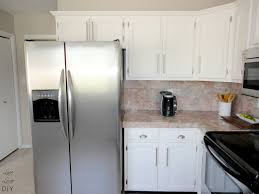diy kitchen remodel with white painting oak kitchen cabinet with door and drawer combined with marble backsplash and countertop plus refrigerator for very