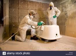 Men wearing protective gear spray painting bathtub Stock Photo ...