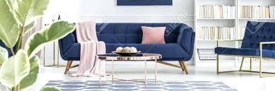navy blue sofa pink pillow on navy blue sofa near armchair in elegant living room interior navy blue sofa