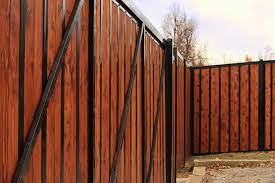 gray composite fence planks with a black metal frame create a clean looking and strong privacy fence to protect inventory and equipment