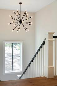 an oil rubbed bronze sputnik chandelier illuminates a white staircase accented with a black handrail