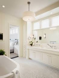 beautiful master bathroom with off white wood paneling off white bathroom cabinets double sinks long mirror calcutta marble countertops white carrara