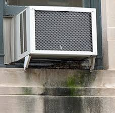 window air conditioner outside. air conditioner in a window on stone building, with discoloration below the outside e