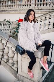 picture of black cropped pants a white sweater a fuzzy faux fur coat and pink sneakers