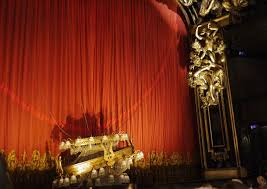 along with the fancy theatre interior decorated with golden colors the red curtain showing perfect color match with the phantom of the opera