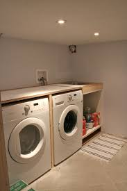 basement laundry room interiors ideas with double white washing machine under wooden countertop with laundry cabinet