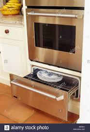 closeup of plates in warming drawer below stainlesssteel oven c53