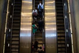 people on escalators. people ride an escalator to exit the metro transit system in washington, d.c. (brendan on escalators d