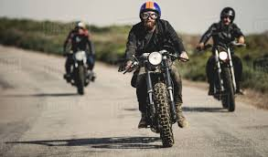 three men wearing open face crash helmets and goggles riding cafe racer motorcycles along rural road