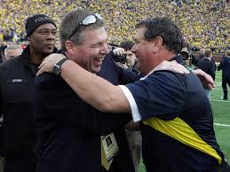 Dave Brandon and Brady Hoke celebrate at midfield after