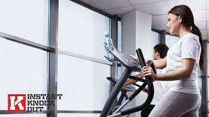 dark haired woman in the gym wearing a white t shirt exercising on an