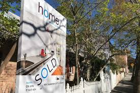 house sold sign outside a row of terraces in the inner sydney suburb of glebe