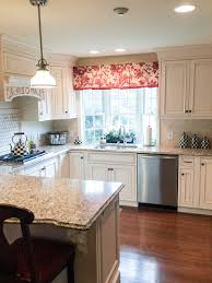this bright kitchen with custom white cabinets has a great floor plan the bay window adds extra light from behind the sink custom wood detail in cabinetry