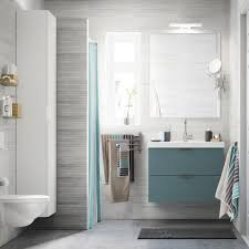 A Light Grey Small Bathroom With A White High Cabinet A Mirror And A Grey