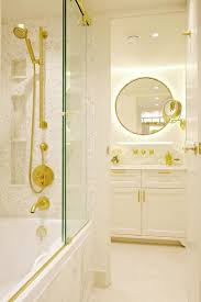 drop in bathtub with sliding glass shower doors on brass rails