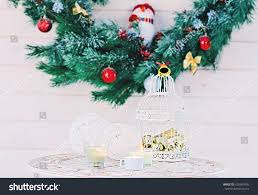 table xmas tree. decorated christmas tree branches, vintage cage with gold balls and candles on table. table xmas