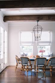 a rounded iron pendant in the same iron finish as the oversized kitchen island pendants keep a consistent flow throughout this open space