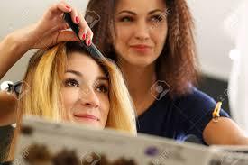 女性美容師手かなりブロンドの訪問者に髪型を作るくしや髪の毛のロックを
