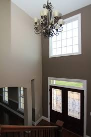 two story foyer with faux candle chandelier two glass front doors hardwood staircase with white painted risers
