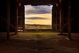 seeing rural landscape through the barn door photography window view of a sunrise