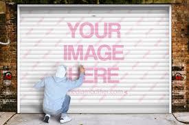 man painting graffiti on a garage door
