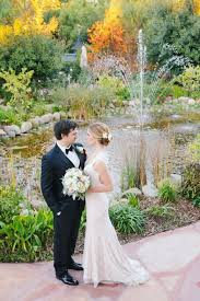 the beautiful pond with fountain sprays surrounded by flowers and greenery is the centerpiece of this fairytale wedding location
