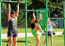 three women exercising on a joint use pull up bar at an outdoor fitness park