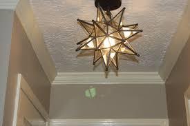 moravian star pendant light on white ceiling with art design