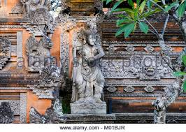stone carvings and statue on the outer wall of a balinese compound in ubud bali on indonesian carved wall art with stone wall sculpture ubud in bali in indonesia in southeast asia
