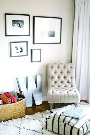 chic nursery features a black and white photo wall over tan linen tufted slipper chair next slipper chair white off upholstery