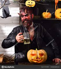 devil or monster partying man wearing scary makeup holds beer stock photo
